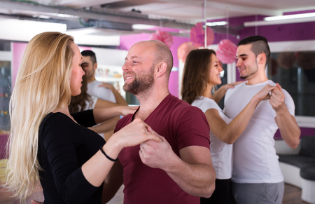 Happy young men and women having dancing class indoors Stock Photo