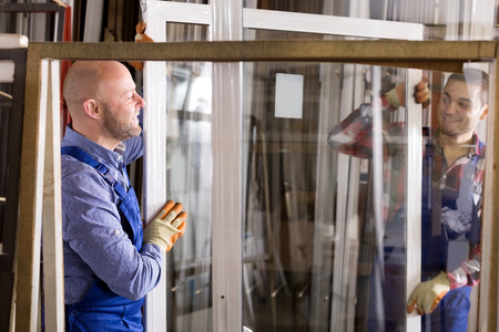 thermoplastic: Adult workmen with windows production at modern factory