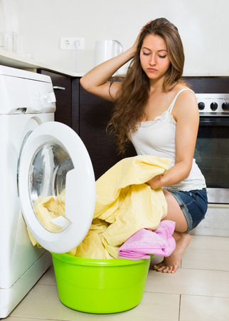 unsound: Home laundry. Tired young female with clothes near washing machine at home Stock Photo