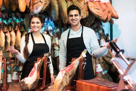 jamones: Dos profesionales de venta de jamón y sonriente en la tienda de delicatessen Foto de archivo
