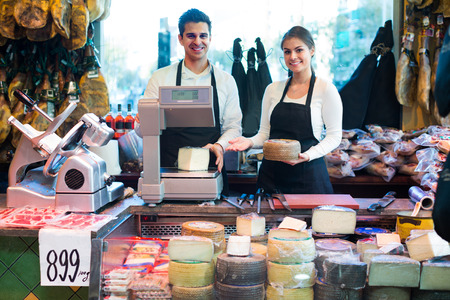 wurst: Portrait of european sellers offering cheese and wurst in shop Stock Photo