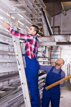 toolroom: Two smiling workers in uniform choosing PVC window profile at stand Stock Photo