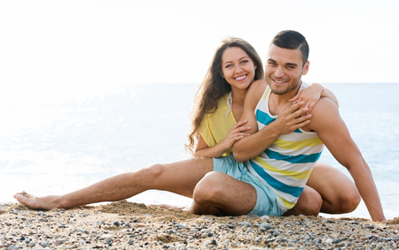 twosome: smiling twosome having romantic date on sandy beach at sunny day Stock Photo