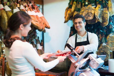 armenian woman: Young cheerful brunette choosing iberico and serrano jamon and smiling Stock Photo