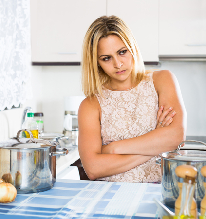 dispirited: Tired adult spanish woman leaning her elbows at the kitchen