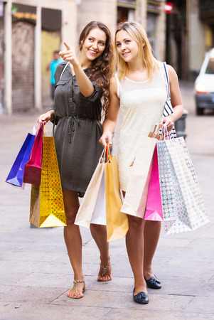 gladful: Laughing american girls carrying bags with purchases outdoors Stock Photo