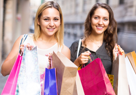 spendthrift: adult girls carrying bags with purchases outdoors Stock Photo