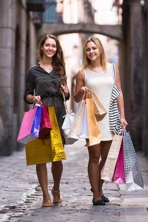 gladful: Two happy young women walking by street with shopping bags