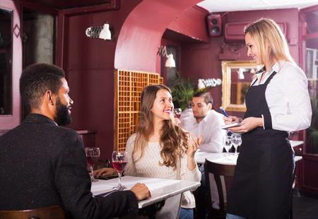 middle class: Happy couple having date in middle class restaurant. Focus on blonde girl Foto de archivo