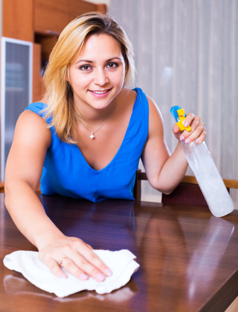 dusting: Portrait of ordinary girl in blue blouse dusting furniture indoors Stock Photo