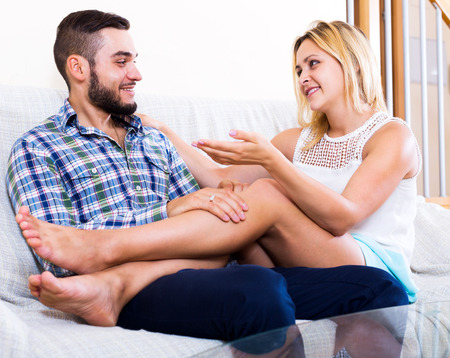 blabbing: Smiling young guy and young woman friendly chatting at home Stock Photo