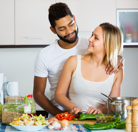 25s: Positive young interracial couple cooking vegetables and laughing in kitchen