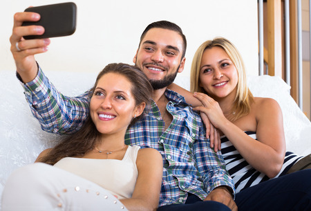 long term: Two smiling girls and young man doing selfie at home