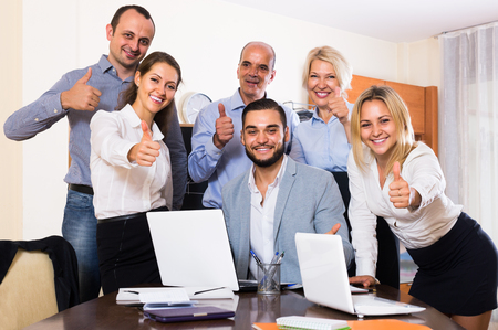 spanish looking: young spanish colleagues looking at laptop and smiling
