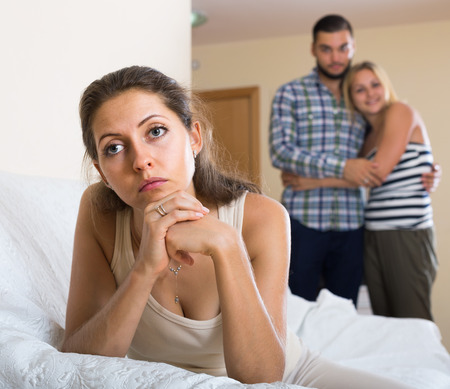 polygamy: sad spanish person keeping silence turned away from friends Stock Photo