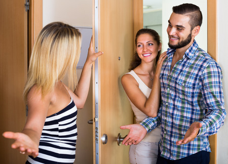 warmly: Young smiling couple warmly greeting friend at the doorway. Focus on guy Stock Photo