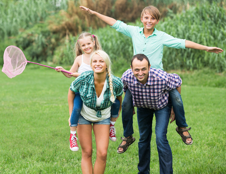 spending: Positive family of four spending summer weekend together at countryside Stock Photo