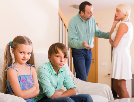 living room boy: sad european children in silence while parents arguing at home
