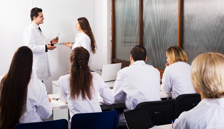 Group of smiling professionals in white overalls at advanced training courses