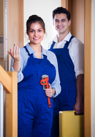 tooling: Happy handyman and female  in uniform with tooling