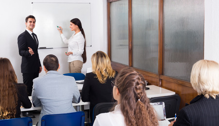 attentive: Attentive students with teacher in classroom at business school