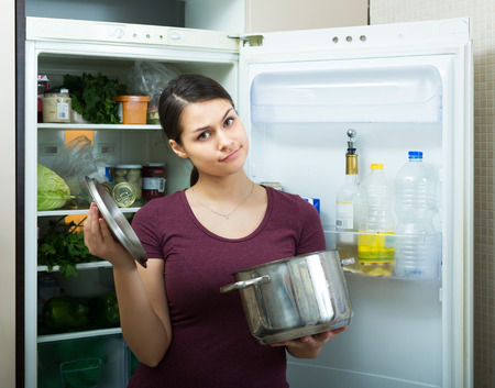 tainted: Amazed young woman sniffing at foul food from casserole