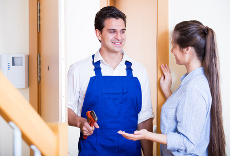 Young woman inviting handyman with tooling to come and help Stock Photo