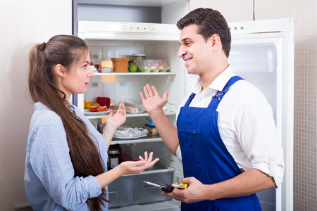 complaining: Worried woman complaining to handyman on problems with refrigerator Stock Photo