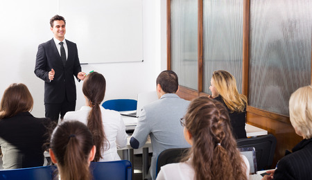 training course: Group of attentive adult students with teacher in classroom at business training Stock Photo