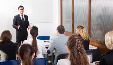 Grupp uppmärksam vuxenstuderande med lärare i klassrummet på företagsutbildning