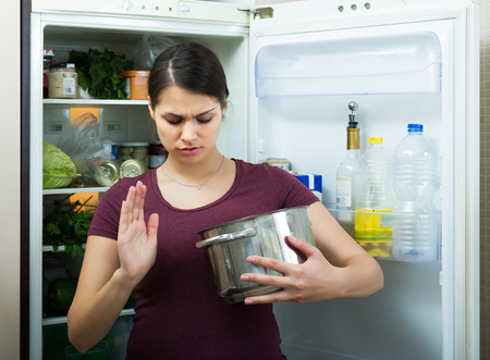 loathsome: Amazed brunette woman sniffing at foul food from casserole Stock Photo