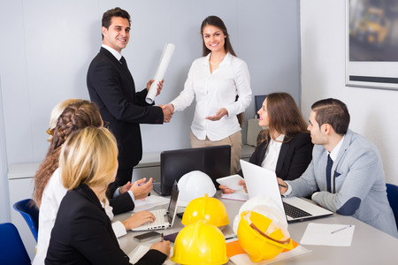 warmly: Successful team of constructors and designers warmly greeting new partner Stock Photo