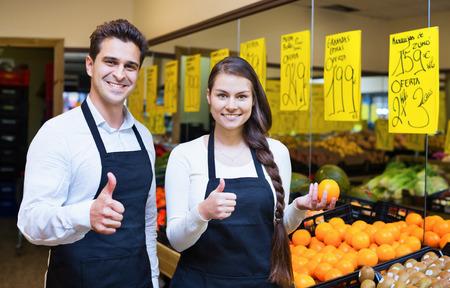 vendedores: Vendedores positivos que ofrecen buen precio para las frutas en la tienda de comestibles Foto de archivo