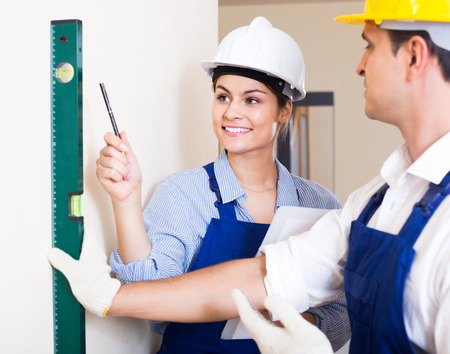 armenian woman: happy spanish specialist and assistant working with wall in new building