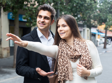 sidewalk talk: Positive american  brunette showing direction to Indian guy at the street
