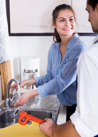 unblock: Professional plumber with tools and housewife smiling in kitchen Stock Photo