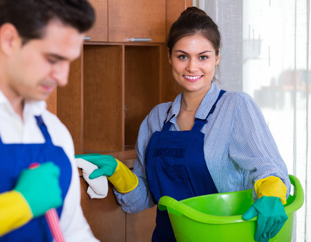 armenian woman: Smiling cleaners team cleaning and dusting in ordinary apartment Stock Photo