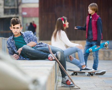 outsider: Jealous russian teen and his friends after conflict outdoors Stock Photo