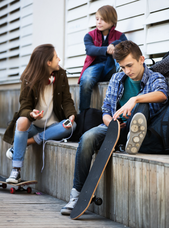 16s: Teenage males and girl relaxing with mobile phones on the street