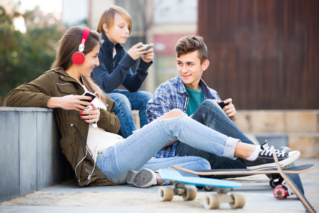 16s: Group of ordinary teenagers relaxing with mobile phones outdoor. Focus on girl