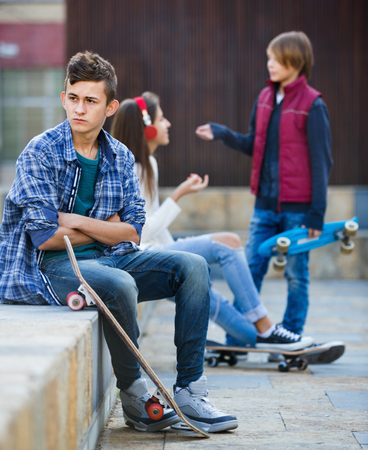 unfaithfulness: Offended boy and happy couple of teens apart on the street