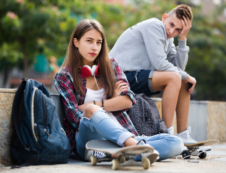 16s: Teenager couple with the skateboards having an argue outdoors