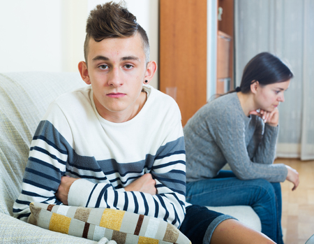 berate: Upset mother and angry son arguing in domestic interior