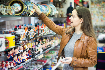 Longhaired young female customer buying things for memory in souvenir shop