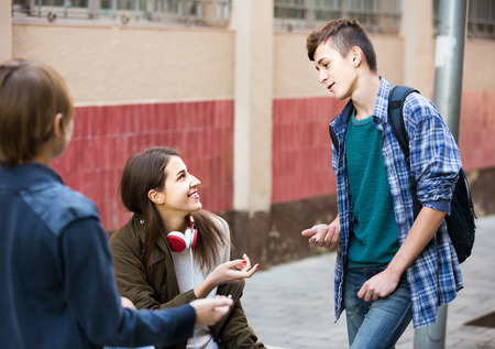 blabbing: Group of smiling teenage friends chatting and having fun outdoor