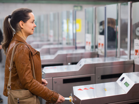 turnstile: Young woman passing the turnstile at  station