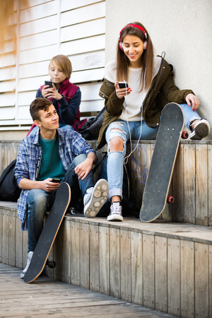 16s: Teenage males and their smiling girlfriend relaxing with mobile phones outdoor