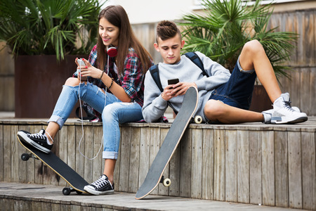 teens playing: Girl and boy teens playing on mobile phones and listening to music outdoors