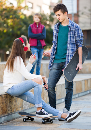 unfaithfulness: upset teen and his friends after conflict outdoors Stock Photo