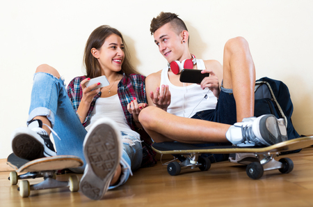 16s: Teenager and his girlfriend with smartphones at home
